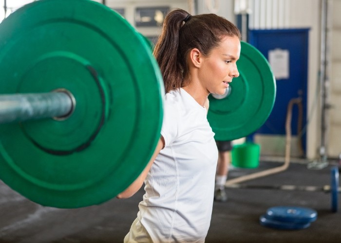 woman doing backsquat with heavy barbell in the gym